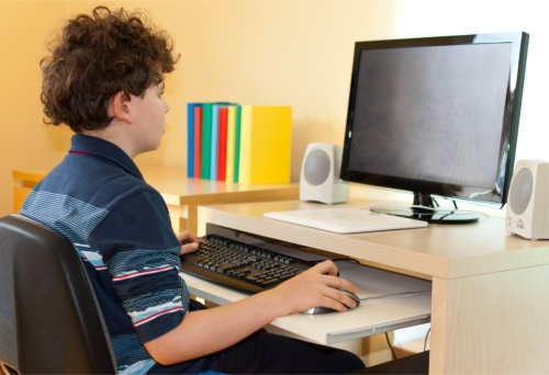 a kid sitting in front of a personal computer