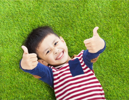 a child lying on the grass showing two thumbs up