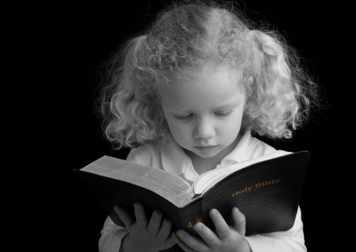 little girl reading holy bible