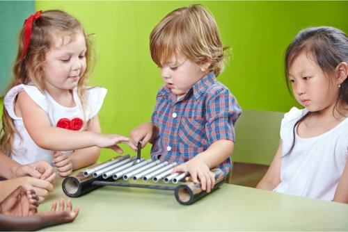 the toddler is playing a musical instrument while others are watching